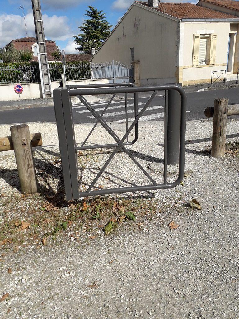 Portique métallique pivotant, en forme de fer à cheval. Deux barrières en bois de chaque côté.